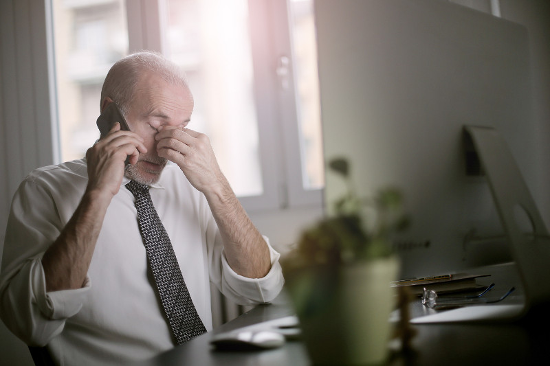 A     stressed man talking on a cell phone.
