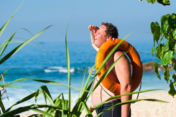A man on a beach,     with a life-preserver over his shoulder. He appears to be looking for     something.