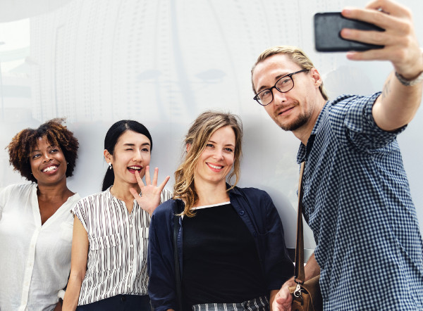 An image of three women smiling for a smartphone picture being taken by the man next to them.