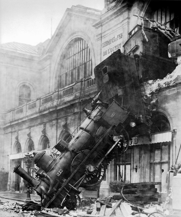 A train train     has burst through the wall of a building and is resting, wrecked, on the     ground.